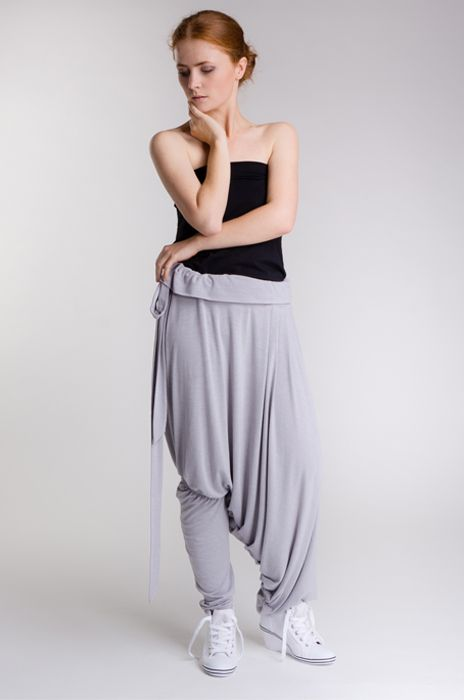 Unique and unconventional trousers. One leg is narrow and elasticated under the knee, while the other is wide and pleated forming   a skirt trouser, tied in the waist with a long narrow belt.   Fabric composition: 94% viscose, 6% elastane.