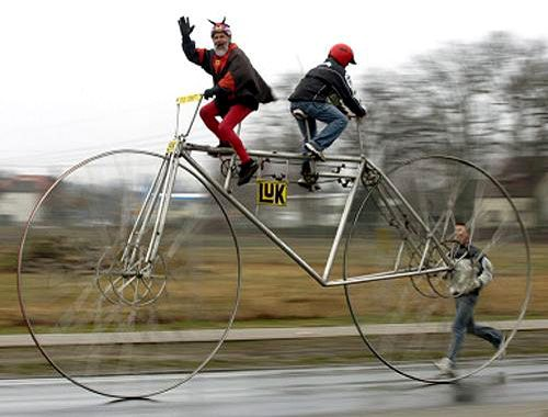 Insane Giant Tandem Bike - looks like it was designed to break every bone in your body. The rear rider peddles facing backwards so guess which bone they will break first? #creditmissing