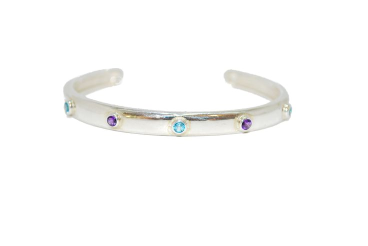 This sterling silver bangle features five gemstones that accentuate around the wrist alternating blue topaz and amethyst.