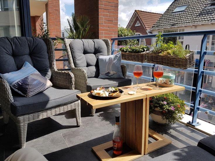 Gemütliche Veranda mit zwei Korbgartenstühlen und einem seitlichen Holztisch. Genießen Sie nach einem …