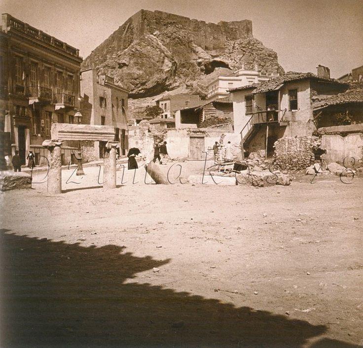 Plaka of Athens, ionic columns,1910 1910 Μπροστά από τον βυζαντινό ναό της Αγίας Αικατερίνης στην Πλάκα οι ιωνικοί κίονες με το επιστύλιο είναι στο μεγαλύτερο μέρος τους βυθισμένοι στις επιχωματώσεις που συσσώρευσαν οι αιώνες. Στο βάθος η πλατεία Λυσικράτους