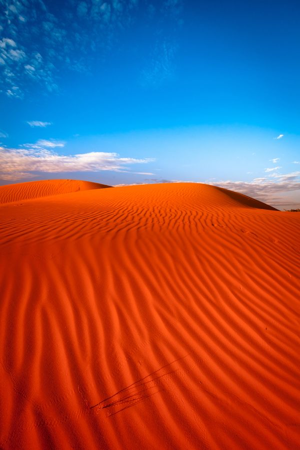 """Red sand dune with ripple and blue sky"" by Oat Vaiyaboon, via 500px."