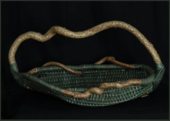 """Blowing in the Wind - Tina Puckett                                        H 13"""" W 27"""" D 14""""                    Contemporary woven sculpture, this basket is framed out                      of bittersweet and woven in dark green reed."""