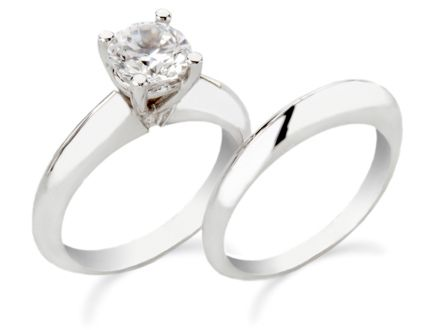 White gold round solitaire engagement ring with matching wedding band.