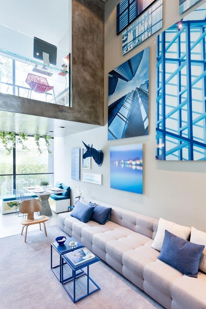"""O mezanino do apê Alvorada funciona como uma varanda: lá em cima, sobre o living, está um escritório, separado da convivência pelo guarda-corpo em vidro temperado (10 mm). A janela dá vista para a rua e os elementos """"de concreto"""", que não são estruturais, foram executados em gesso acartonado e receberam pintura (cal, tinta branca e cimento) que imita o material. O projeto de interiores é do escritório Suite Arquitetos"""