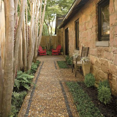 Small Side Patio - The pebbled border adds texture in this cozy side-yard path and patio. A pair of planters and a bench half-way down the path breaks up the space.