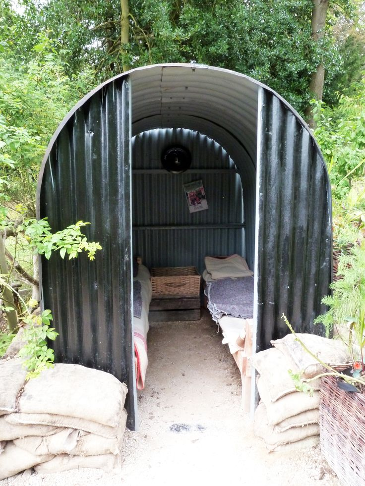 Anderson shelter in Chatsworth Castle Park, UK. Air-raid shelter made in WWII in UK. 6 people can live in it. The structure is made to deform. Low cost shelter. Biggest problem: cold and flood