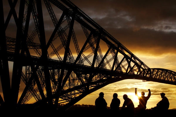 Members of the repainting team sit in front of the Forth Bridge in North Queensferry near Edinburgh, Scotland. Network Rail announced the end of the 10 year refurbishment and repainting of the bridge, on which over 240,000 liters of paint was used.