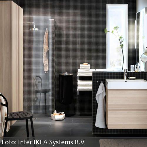 Schwarze Mosaikfliesen und helle Holzschränke im modernen Badezimmer