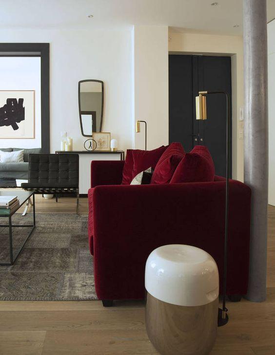 Ce canapé rouge bordeaux en velours est très élégant avec le gris charbon de la porte et du fauteuil, pour une déco très chic
