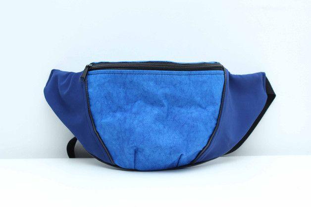 Środek oraz górna klapka nerki wykonane zostały z niebieskiego papieru*, boki oraz tył to chabrowy nubuk. Podszewka wykonana z grubej, bordowej tkaniny bawełnianej, natomiast kieszonka oraz górna...