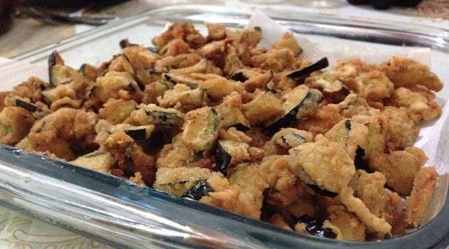 1 berinjela com casca cortada em cubos  - 1 colher (sopa) rasa de sal  - 1 ovo  - Orégano a gosto  - Farinha de trigo e farinha de rosca para empanar  - Gotas de limão ou vinagre