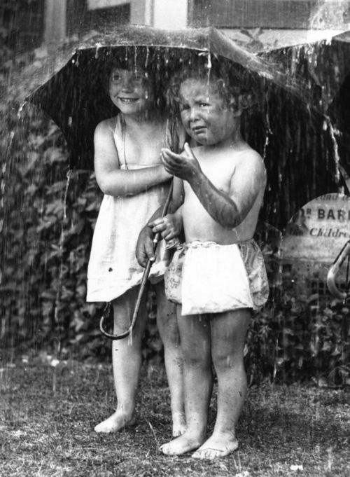 Two young children at Dr Barnardo's sheltering under an umbrella from a garden shower.  Fox Photos/Getty Images, 21st June 1934