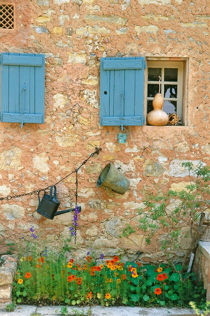 Old gardening tools are strung above a cluster of nasturtiums at one Provence home.
