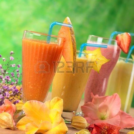 Frische Papaya, Mango, Erdbeere und Ananas Fruchtsäfte und Milchshakes mit Blumen (Selective Focus, Focus auf dem Papaya-Saft und der Papaya Scheibe Beilage) dekoriert