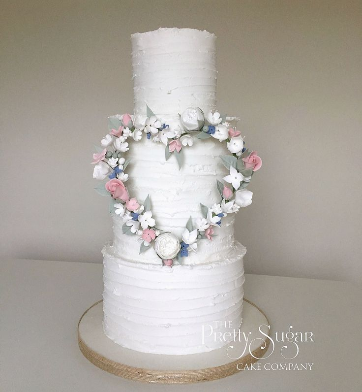 Rustic iced wedding cake with sugar flower heart