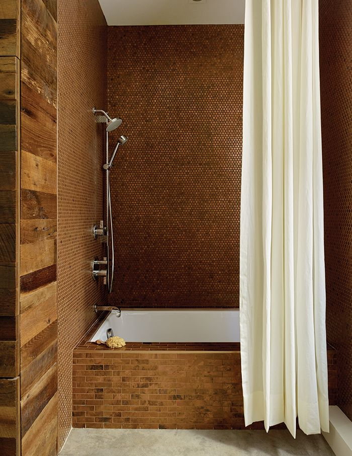 The walls are clad with metal penny tile in the Antique Copper finish from Design and Direct Source of Portland, Oregon. Linear-format tiles in the same finish line the tub.