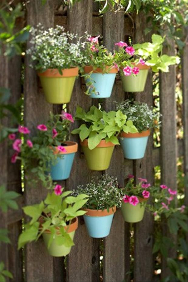 paint terracotta pots and attach them to your fence...I'll have to figure out how to attach them to your fence so they are floating like this, but I'm sure its not too hard. ^.^