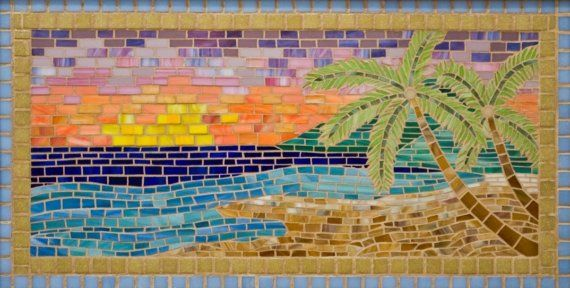Paradise is a scene with mountains behind palm trees, water, sand and a beautiful sunset. Hand cut stained glass is the main material with