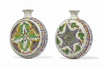 A KUTAHYA POTTERY PILGRIM FLASK OTTOMAN TURKEY, 19TH CENTURY Of typical form with rounded body and flattened sides, rising to thin cylindrical neck with flaring mouth, the white ground painted in green, yellow, manganese, blue, bole-red, one side with a winged cherubim surrounded by cusped hanging medallions, the other side with stellar motif surrounded by fish, [one] side with inscription in Armenian bordered by red bands and polychrome scrolling vine, intact 7 1/8in. (18cm.) high