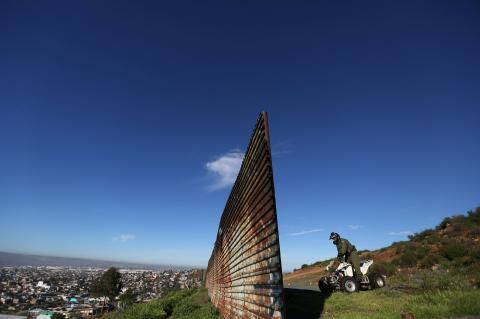 》Lücke im Zaun zwischen Mexico und den USA: Ein Mitglied der US-Grenzkontrolle inspiziert auf seinem Quad den Zaun zwischen den USA und Mexiko. Am Rand der Stadt Tijuana ist der Wellblechzaun unterbrochen.《