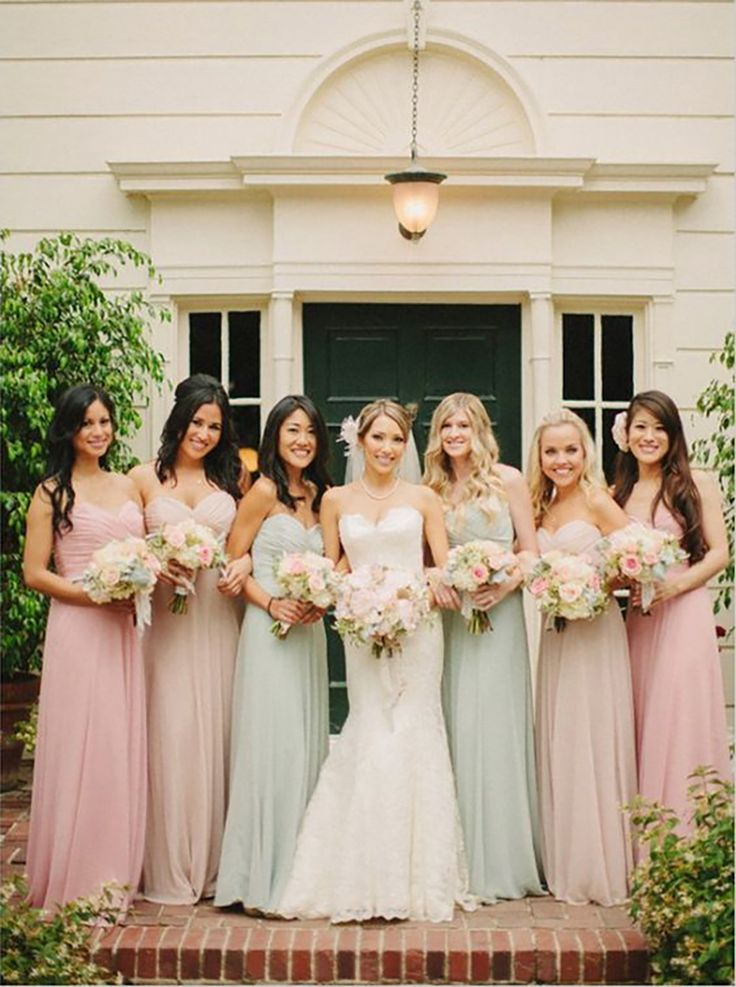 Bride posing with bridesmaids wearing sage, pink and peach