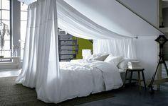 Ein Bett mit weißer Bettwäsche unter einer Dachschräge. Mit weißer Meterware, die an der Decke befestigt ist, entsteht ein Betthimmel.