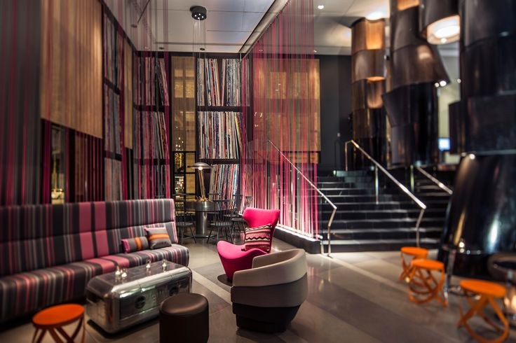 """W Hotel Lobby in Seattle, redesigned by Jeff Kovel and Skylab Architecture- Flavorpaper's Jon Sherman custom designed 'Wax Stacks' wallpaper displaying 7' high stacked records on shelves. """"The effect is staggering and you feel like you have entered an Alice in Wonderland scene but with Alice in Chains as the host"""""""
