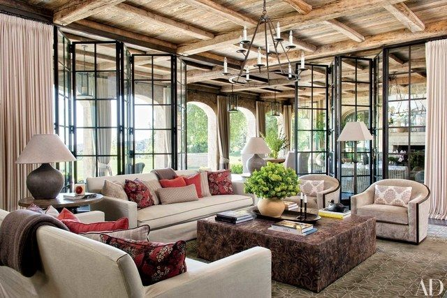 In Gisele Bündchen and Tom Brady's eco-conscious house in Los Angeles, the family room, which opens onto a verdant backyard, is furnished with sofas upholstered in a Castel cotton; the ottoman table is covered in an embossed Bordoni leather from Richard Shapiro/Studiolo.
