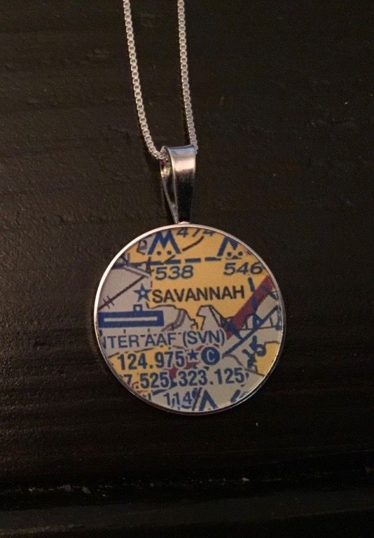 "Savannah, GA: Aviation Map Pendant.   The length of the sterling silver venetian box chain necklace measures 16"" and the pendant is approximately 1"" in diameter. The necklace and pendant tray are sourced from an American supplier and are certified Made in the USA. The map comes from an air navigation sectional chart, which is used by pilots. You do not have to be an aviation enthusiast to use this necklace. But it helps.  The aviation map pendant is a recommended gift for pilots or…"