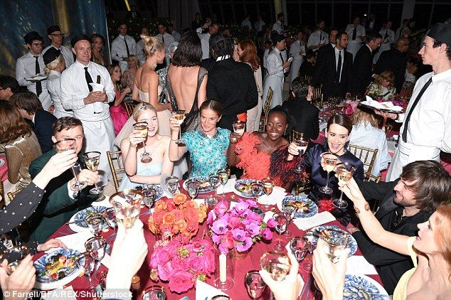 Party: Elle Fanning was photographed during Monday night's Met Gala, sitting down at a table and holding up her glass to cheers with the other guests