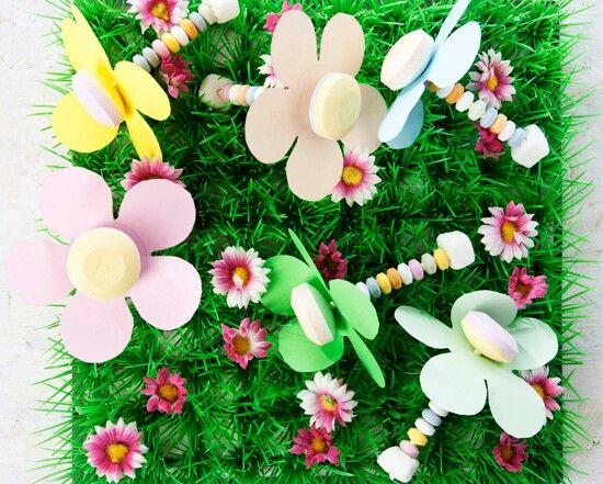 Dit heb je nodig  lolly's  Snoepkettingen  Tumtum  Gekleurd papier  Schaar    Zo maak je het  Knip bloemen uit het papier. Steek de lolly door het midden van de bloem. Rijg de kraaltjes van de snoepketting aan het stokje van de lolly. Sluit af met een tumtummetje.