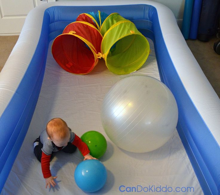 Indoor gross motor play with balls in a baby pool playpen. CanDo Kiddo