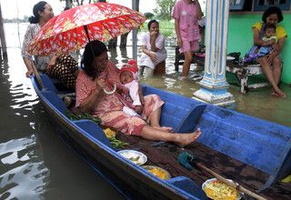 Residents use wooden boats to escape their flooded houses in Pasuruan, East Java, on Feb. 2, 2017. (Antara Photo/Umarul Faruq)