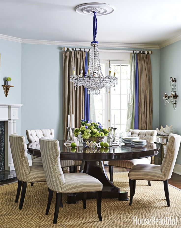 an antique chandelier presides over the pale blue dining room