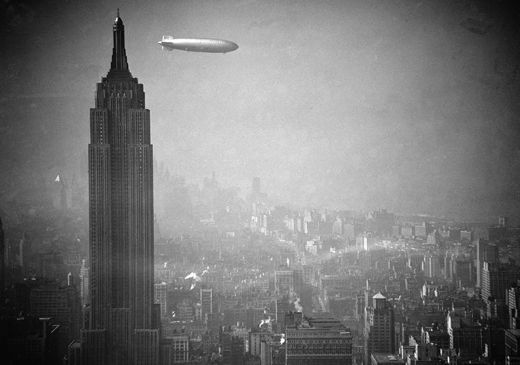 The zeppelin Hindenburg floats past the Empire State Building over Manhattan on…