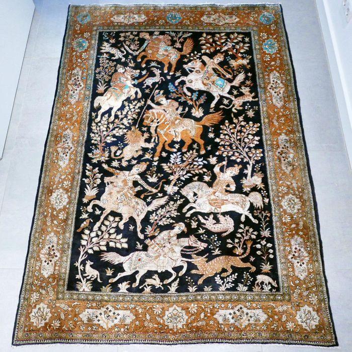 Maak kennis met deze bijzondere Ghom. Het tapijt is ca. 80 jaar oud en verkeert in voor zijn leeftijd in zeer goede conditie en heeft weinig gebruikerssporen. Het tapijt geeft een prachtige jachtvoorstelling weer en is volledige gemaakt van zijde. De donkere kleurstelling en de lichte accenten maken het tapijt zeer uniek. ABSOLUUT EEN WAARDEVOL VERZAMELOBJECT.  Formaat ca. 192 x 136 cm.  Knoopdichtheid is ca. 600.000 kn/m2.   Bekijk de foto's en laat u overtuigen. Wordt geleverd met ...