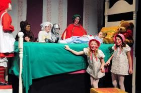"""In Topeka Civic Theatre & Academy's youth produciton of """"Raggedy Ann and Andy,"""" the toys, left to right, Raggedy Ann (Abby Musick), Bruin (Carter Phillippe), Grandma (Elizabeth Seitz), Mechanico (Lilia Potter), Susy Pincushion (Kelli Kychik), and the Twin Baby Dolls (Kate Roeder and Halle Pavlik) gather to marvel at the new arrival, a French doll named Babette (Rachel Gaul), in the bed."""