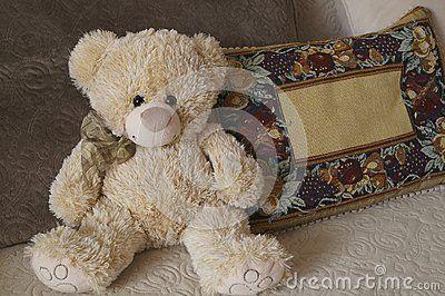 Sweet teddy bear between pillows