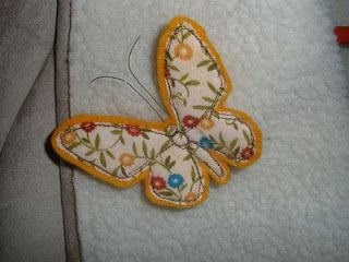 I traced the pattern onto the fusible applique paper in reverse - actually I forgot to do it in reverse :) Then ironed it onto a large piece of felt and fre motion sewed the edges and the details. I trimmed around the felt leaving a 1/8' border. Sorry the pictures don't match. I reused the tea cosy ones.