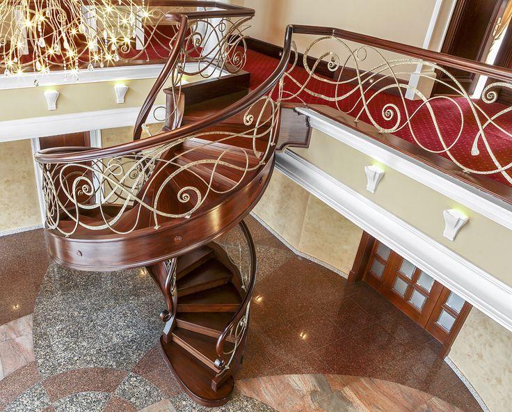www.trabczynski.com ST433 -Spiralne schody gięte z podstopniami, wykonane z barwionego mahoniu sapelli. Bogato zdobione policzki. Ręcznie kute stalowe balustrady z pochwytami drewnianymi. Realizacja wykonana w prywatnej rezydencji , projekt – Robert Kiona & TRĄBCZYŃSKI / ST433-Spiral stair with risers, made of stained Sapele mahogany. Exquisitely decorated stringers. Hand-wrought steel balustrades, wooden handrails. Private residential project, designed by Robert Kiona & TRABCZYNSKI.