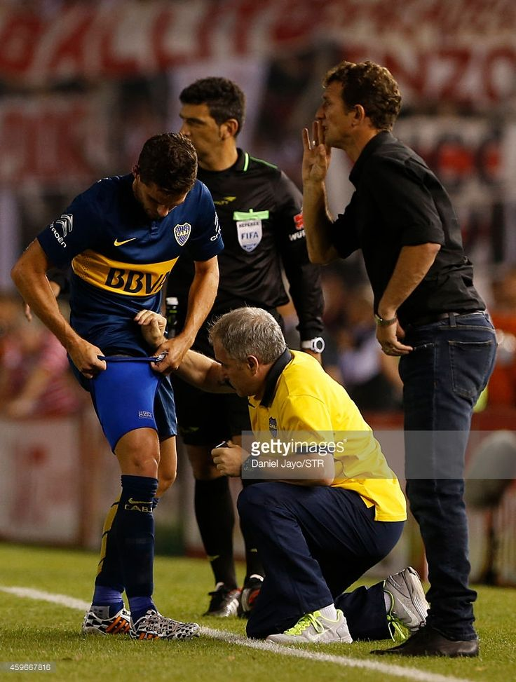 Fernando Gago, of Boca Juniors, (L) receives medical attention during a second leg semifinal match between River Plate and Boca Juniors as part of Copa Total Sudamericana 2014 at Monumental Antonio Vespucio Liberti Stadium on November 27, 2014 in Buenos Aires, Argentina.