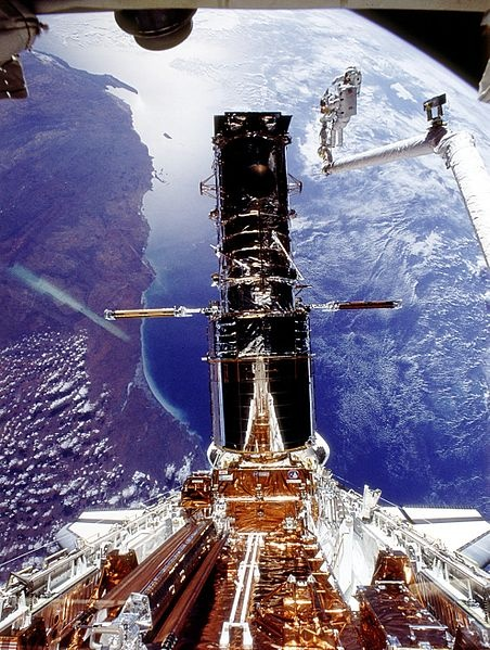 """Shuttle STS-61 onboard view: Hubble Space Telescope (HST) repair. Repair of the Hubble Space Telescope (HST) - orbiting earth at an altitude of 325 nautical miles. Perched atop a foot restraint on shuttle Endeavour's remote manipulator system arm, astronauts Story Musgrave and Jeffrey Hoffman wrap up the final of five space walks. Date of Image: 1993-12-09""."