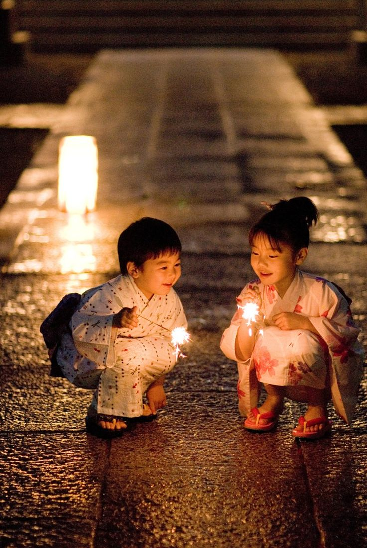 Japan - Little boy and girl with sparklers on summer night.
