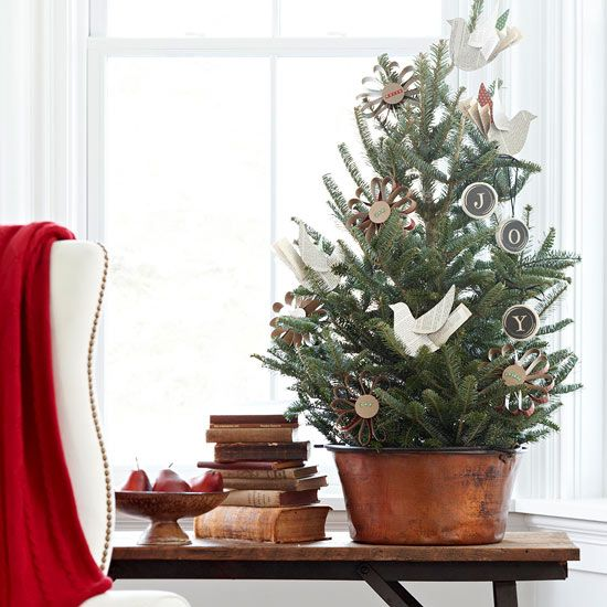 Rustic Tabletop Christmas Tree: Create an old-fashioned look for a side table with a 3-foot-tall tabletop Christmas tree in a copper pot. Adorn the tree with simple paper ornaments and display next to a stack of old books for rustic character.
