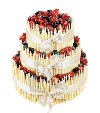 Speciální dort 13 Třípatrový dort, o rozměrech 18 cm, 24 cm a 32 cm, dozdoben bílými čokoládovými ruličkami, čerstvým ovocem a saténovou stuhou.