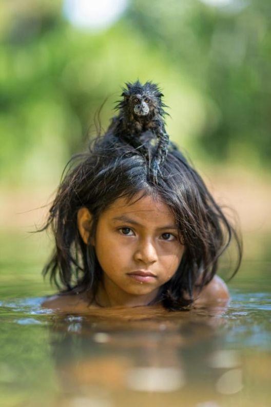 A jovem Yoina Mameria Nontsotega, do povo indígena peruano Matsigenka, carrega seu sagui de estimação na cabeça enquanto nada pelo rio Yomibato, no Peru (fotografia de Charlie Hamilton James)