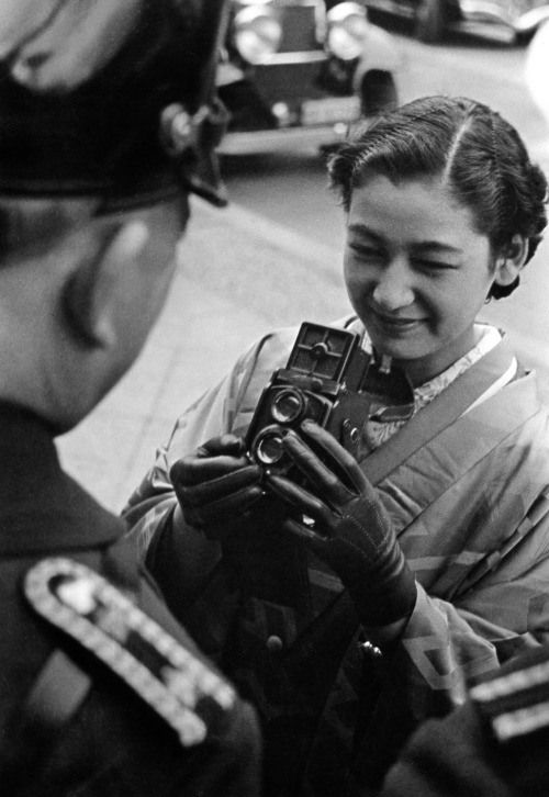 Setsuko Hara is photographing a policeman with her Rolleiflex camera during her visit to Berlin in 1937. She was there to promote the film Daughter of the Samurai (1937) - a co-production between Japan