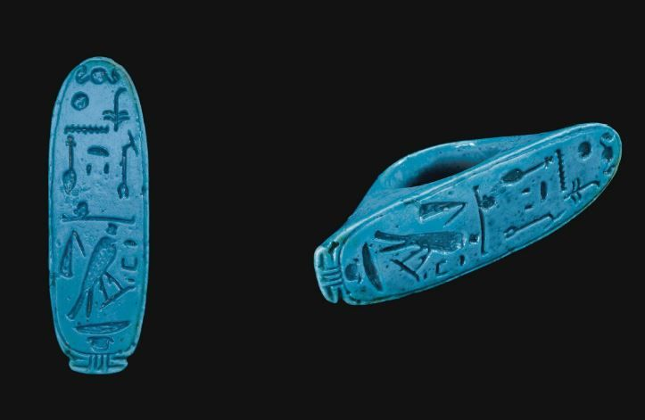 "Egyptian faience finger ring, Third Intermediate period, 21th-22th Dynasty, 1070-712 B.C. Bright blue in color, with a plain hoop expanding to the large cartouche-shaped bezel, enclosing a hieroglyphic inscription, reading ""King of Upper and Lower Egypt Khonsu  Thebes Nefer-hotep, Falcon of Gold"", 6.9 cm long. Private collection"