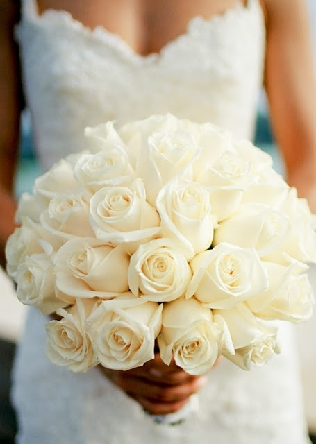 I think Im going to go with white roses for our bouquets and then just get artificial flowers and bouquets for décor